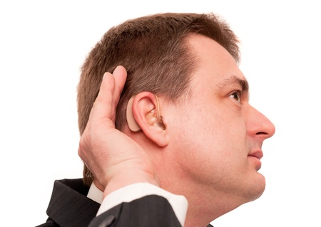 Deaf man wearing hearing aid listening for a quiet sound. Isolated on white.