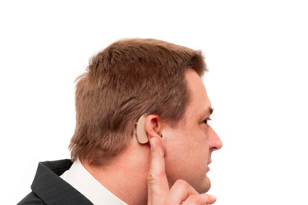 Deaf man showing his behind-the-ear hearing aid. Isolated on white.