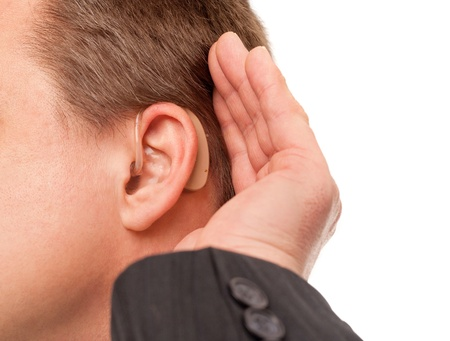Close up ear of a middle aged businessman wearing hearing aid and listening for a sound