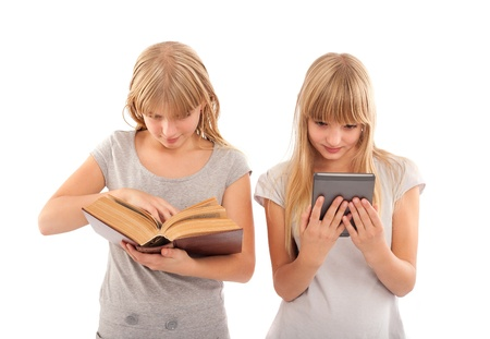 Two girl reading books - traditonal and ebook ones  photo