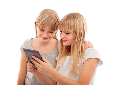 Young females reading something funny in an ebook reader tablet device.