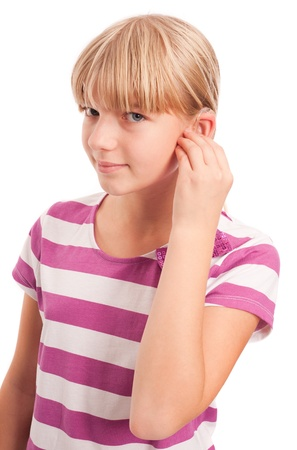 Hearing aid - Young Girl setting her hearing aid. Isolated on white. photo