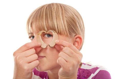 hearing aid: Young female looking through a heart shape forming from two hearing aids