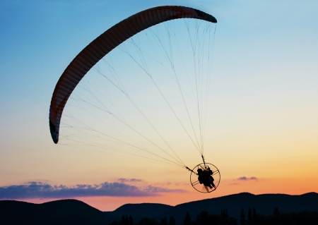 Paragliding over the hills at sunset Stock Photo