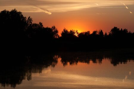 Vivid sunset with a lake and trees