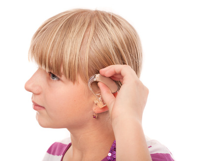 Teenage girl inserting a hearing aid in her ear  Studio shot isolated on white