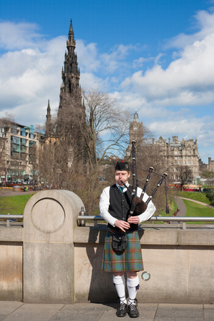 Edinburgh, UK - APRIL 25, 2013  Scottish Bagpiper playing music with bagpipe at Edinburgh in Scotland