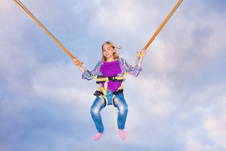 Girl jumping with trampoline jumping rope Imagens