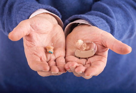 Old mans hand showing a CIC (completely in canal) and a BTE (behind the ear) hearing aids