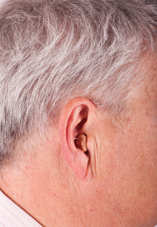 Close-up of a senior mans ear wearing a CIC (Completely In the Canal) hearing aid