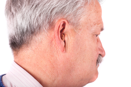 Portrait of a senior man wearing a CIC (Completely In the Canal) hearing aid photo