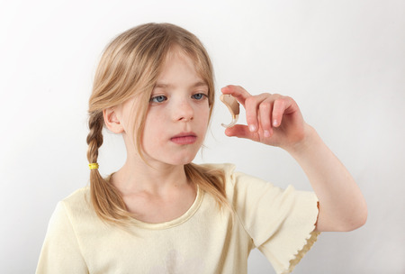Cute girl looking at a  hearing aid. Focused on the hand and the hearing aid. photo