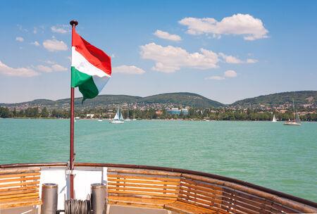 balaton: Lake Balaton from a ship deck with a hungarian flag in Hungary. Stock Photo