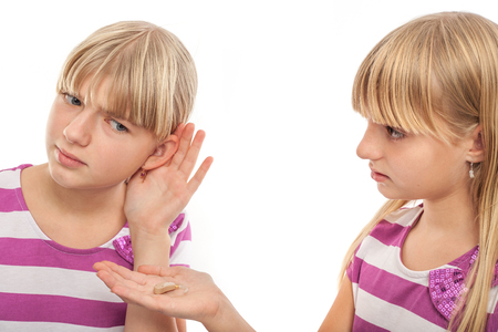 Solution for hearing problems - Girl offering a hearing aid to her girlfriend who cant hear well. Studio isolated on white. Stock Photo