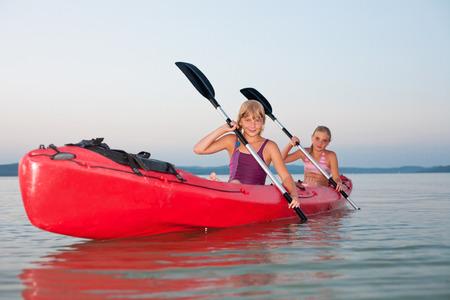 canoa: Las niñas con pala y kayak en un lago al atardecer