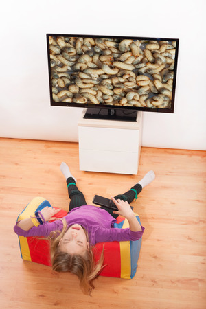 disgust: Kid turning away in disgust not to wathc disgusting worms on the TV.
