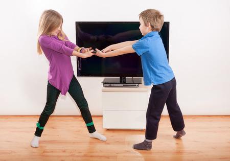 peleando: Hermanos peleando por el teledirigido delante de la TV