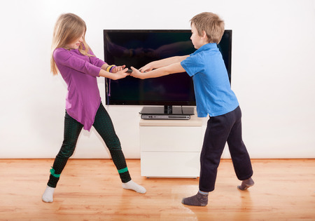 sibling rivalry: Sibling fighting over the remote controll in front of the TV Stock Photo