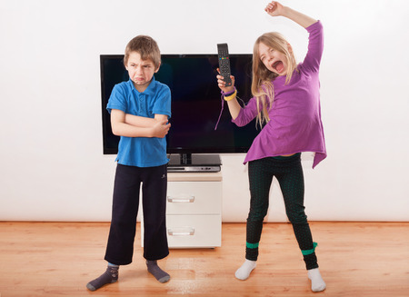 siblings: Winner in the fighting for the remote control - Sister happy with it but her brother is very upset. Stock Photo
