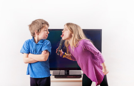 Siblings quarreling over the remote control in front of the television Stok Fotoğraf