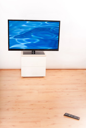 lowboard: Living room with TV and a remote control on the floor