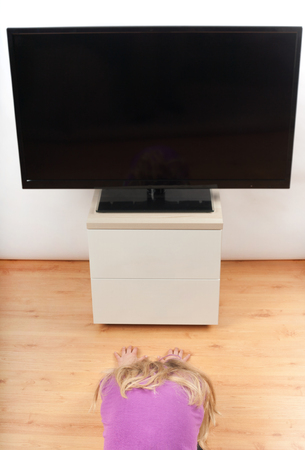 mesmerized: Kid loves TV too much Stock Photo