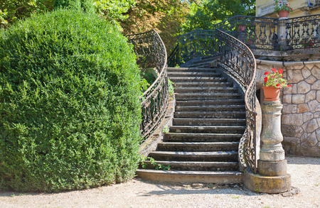 banister: Old stone stairway of a palace with wrought iron banister in a park Editorial