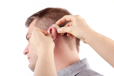 Hands inserting a hearing aid into a mans ear - isolated on white photo