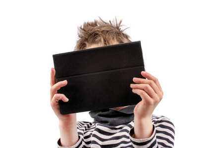 Geek kid holding a tablet device in front of his face photo