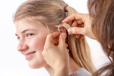 Woman inserting a hearing aid into a young girls ear in front of a white background