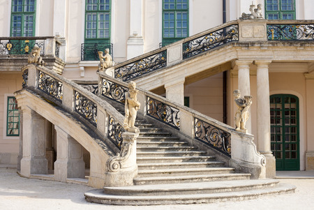 Old stone stairway of Esterhazy Castle with wrought iron banister and statues in Fertod, Hungary