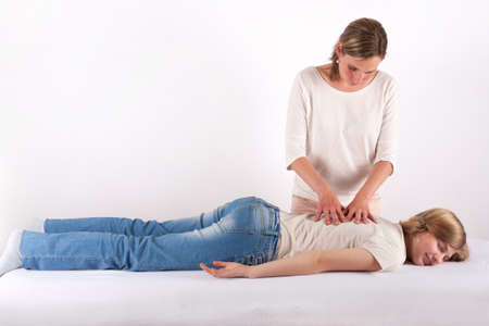 Young girl receives back massage (Bowen therapy)