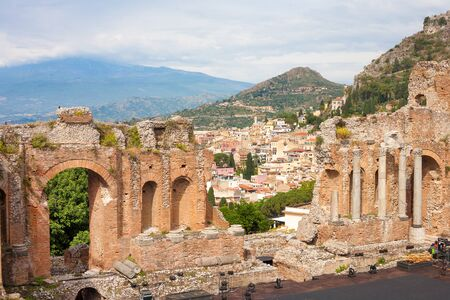 The ancient -roman-greek amphitheatre with the city ant the Etna volcano in the back in Taormina city, Sicily, Italy
