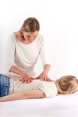 alternative practitioner: Young girl receives Bowen therapy - back massage Stock Photo
