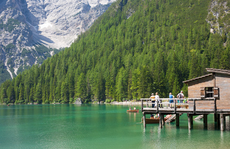 sudtirol: LAKE BRAIES, ITALY - JUL 03, 2015: Tourists boating at Lake Braies in the Dolomites with the Seekofel mountain in the background, Sudtirol,Italy