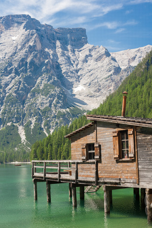 sudtirol: Wooden hut on Lake Braies in the Dolomites with the Seekofel Mountain in the back in Italy (Sudtirol) Stock Photo