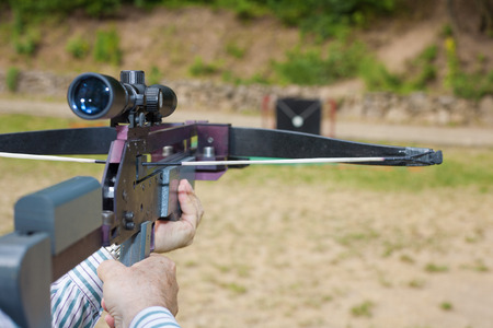 arbalest: Man targeting with a scoped crossbow