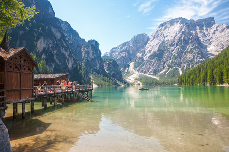 sudtirol: LAKE BRAIES, ITALY - JUL 03, 2015: Tourists walking around the hut at Lake Braies in the Dolomites with the Seekofel mountain in the background, Sudtirol,Italy