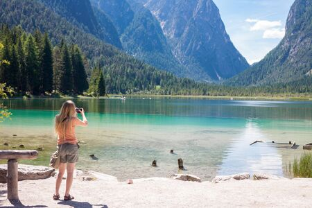 compact camera: Nice girl taking photo with compact camera while on lake Toblach in south Tyrol, Italy