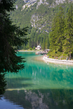 sudtirol: Lake Braies with tourist path, hut and a church in the Dolomites, Sudtirol,Italy Stock Photo