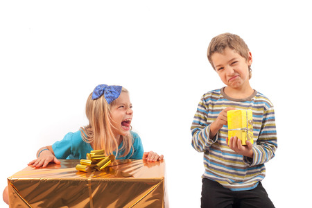 Unfair gift giving between siblings: the girl with big present box is gloating because her brother has only a very small gift box. Isolated on white.