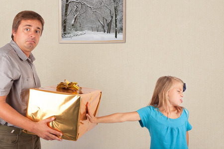 rejection sad: Young girl refusing gift box from her father