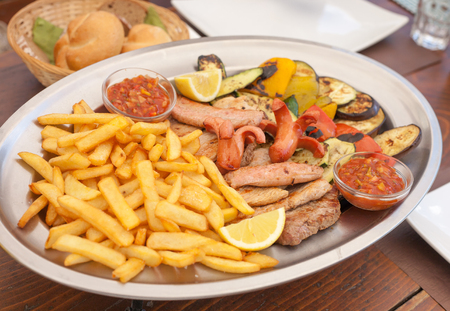 french fries plate: A big plate of sousages,  french fries, sauce and bread - typical meal from the South Tyrol in Italy Stock Photo
