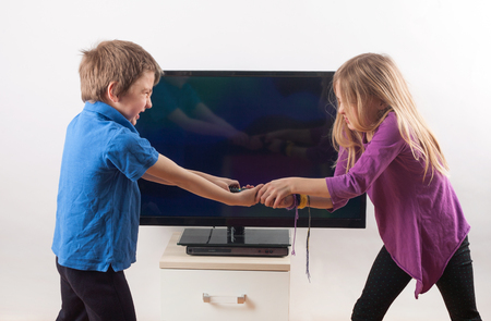Siblings fighting over the remote control in front of the TV Foto de archivo