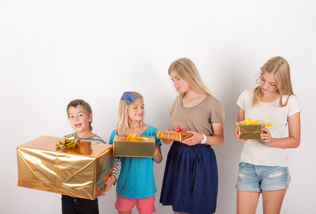 he   my sister: Four siblings comparing their presents. The smallest brother has the biggest gift so he is happy when his older sister not so much. Stock Photo