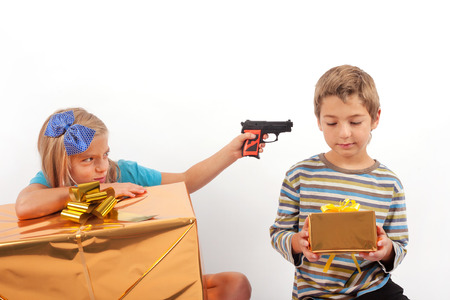 unjust: Brother and his jealous sister - the small brother is more happy with a smaller gift box than his sister with a big one and she targeting a toy gun at her brother to kill him symbolically