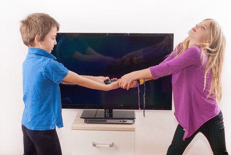 sibling rivalry: Girl and boy siblings fighting over the remote control in front of the TV Stock Photo
