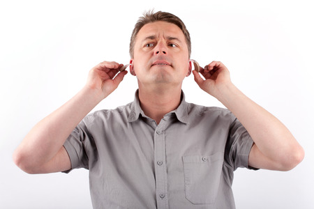 aids: Middle-aged man setting his hearing aids. Stock Photo