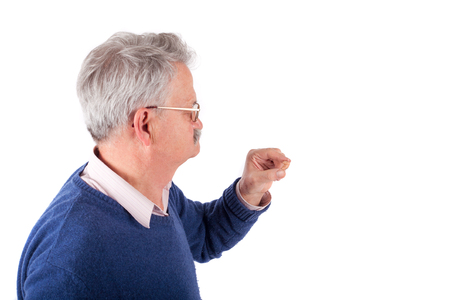 Senior man holding his CIC hearing aid between his fingers photo