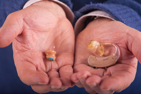 Senior's hands showing behind-the-ear and completely in the canal  hearing aids
